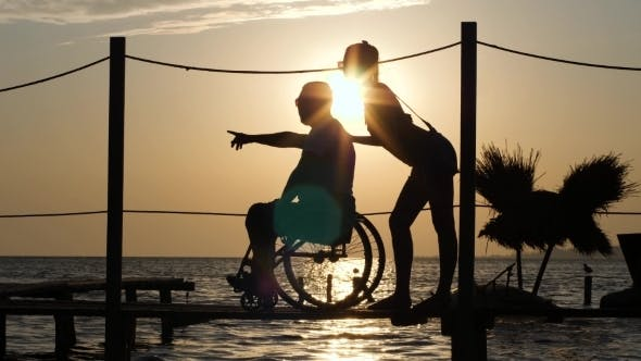 Cover Image for Lucky Disabled with Girlfriend Look Into Distance and Shows His Arms To Horizon on Background Sunset