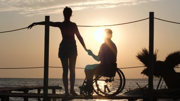Thumbnail for Girl with Friend Handicapped Holding Hands Stand on Pier and Look at Sunset