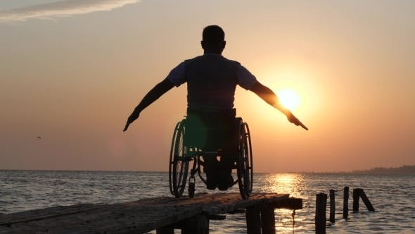Thumbnail for Diseased Man in Wheelchair Relaxes and Lift His Hands Backdrop of Orange Sky on Summer Trip