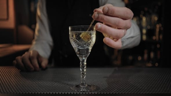Thumbnail for Bartender Adds Olive To Neat Dry Martini Cocktail