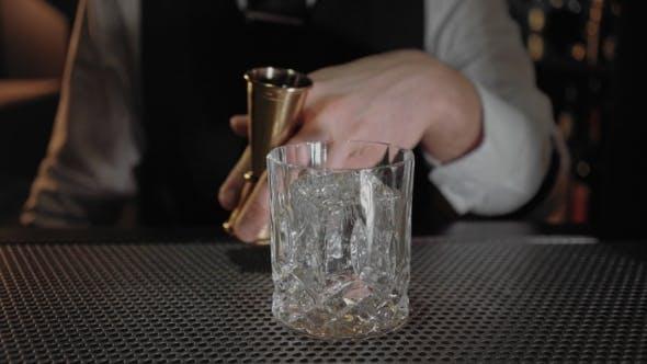 Thumbnail for Professional Bartender Uses Jigger Glass for Cocktail