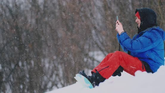 Thumbnail for Male Snowboarder Sitting on the Snow Taking Photos on the Phone Beautiful Scenery