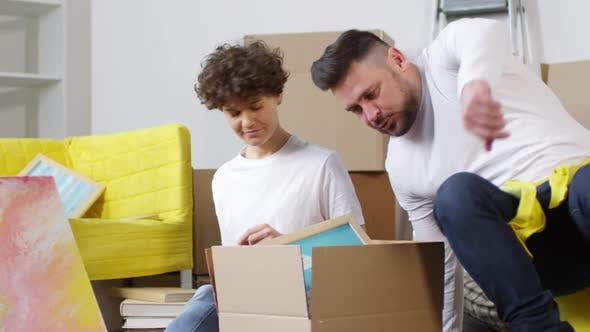 Cover Image for Cheerful Caucasian Couple Unpacking Wall Art in New Flat
