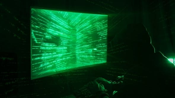 Thumbnail for A Man Hacker in a Hood in a Dark Room Works with the Program Code