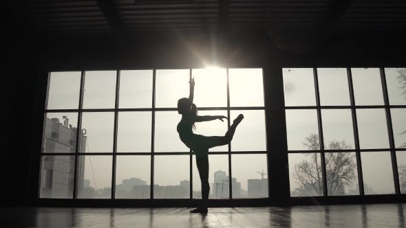 Thumbnail for Silhouette of an Athlete Against the Background of a Large Window. Sports Girl Doing Warm-up Before