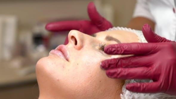 Thumbnail for Cosmetologist Rubs the Female Skin Cream Under the Eyes. Applying Skin Cream Under Eyes.