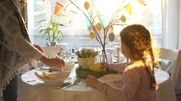 Thumbnail for Woman and Her Little Daughter Are Setting Easter Festive Table with Bunny and Eggs Decoration