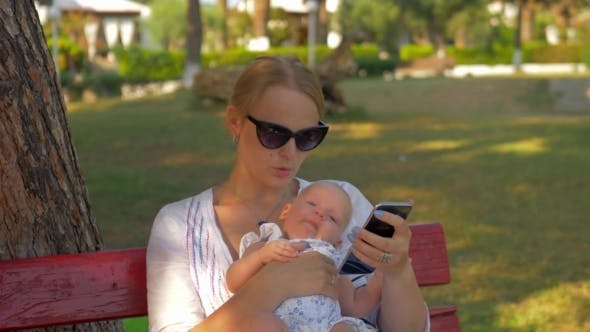 Thumbnail for Woman Using Mobile During Outing with Baby in the Park
