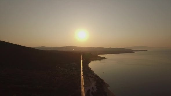 Thumbnail for Flying Over Trikorfo Beach Shoreline and Waterfront Road at Sunset, Greece