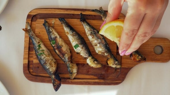 Thumbnail for Pouring Lemon Juice on Grilled Sardines
