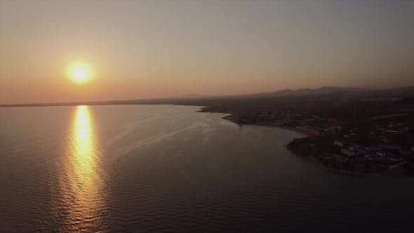 Thumbnail for Sea and Coastal Town at Sunset, Aerial. Distant View of Trikorfo Beach, Greece