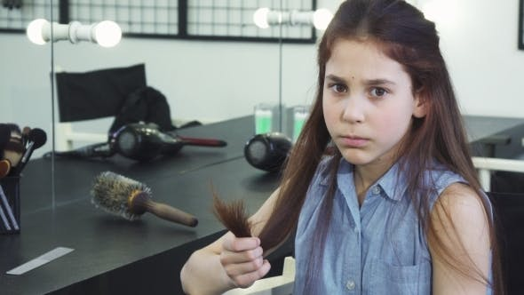 Thumbnail for Little Cute Girl Looking Sad Examining Her Damaged Hair with Split Ends