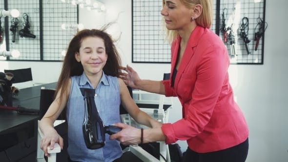 Thumbnail for Happy Little Girl Enjoying Her Hair Being Dried by a Hairdresser at the Salon