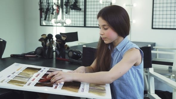 Cover Image for Pretty Little Girl Examining Hair Dye Color Chart at the Beauty Salon