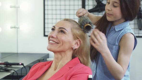 Cover Image for Gorgeous Happy Woman Enjoying Getting a New Hairstyle By Her Cute Daughter