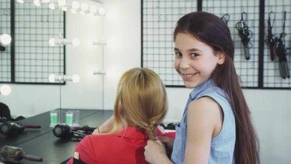 Thumbnail for Cute Cheerful Little Girl Braiding Hair of Her Mom Smiling To the Camera