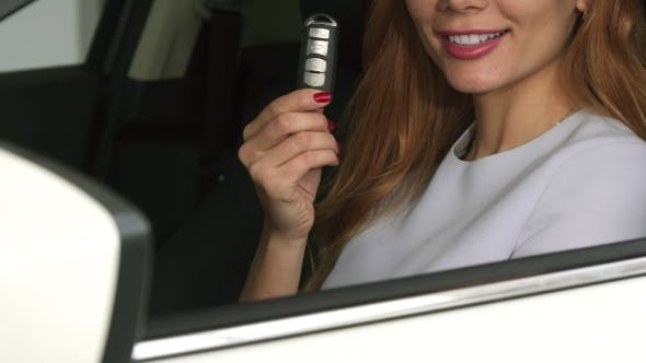 Thumbnail for Cropped  of a Cheerful Female Driver Showing Car Keys Sitting in an Automobile