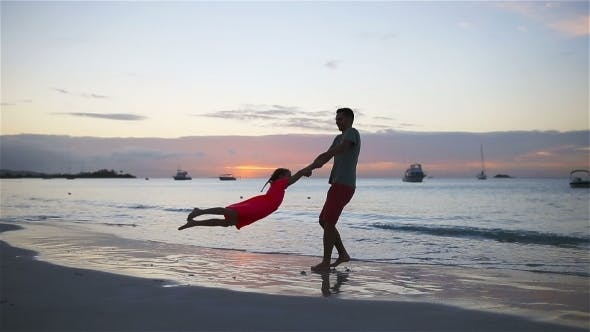 Thumbnail for Smiling Father and Adorable Child Playing at Sandy Beach on a Sunny Day