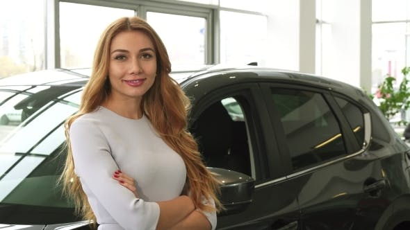 Thumbnail for Young Beautiful Woman Smiling To the Camera Standing at the Car Dealership