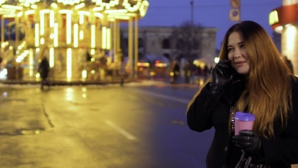 Thumbnail for Young Emotional Woman Talks on Phone at the Carousel Background