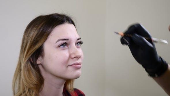 Thumbnail for Masculine esthéticienne dans des gants noirs faisant la procédure de maquillage permanente sur les sourcils féminins esthéticienne