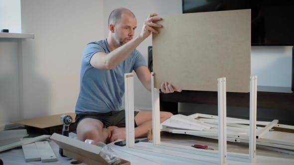 Thumbnail for Geschickter Mann ist Montage Details des neuen Tisches in einem Raum sitzt auf einem Boden zwischen Teilen, Karton