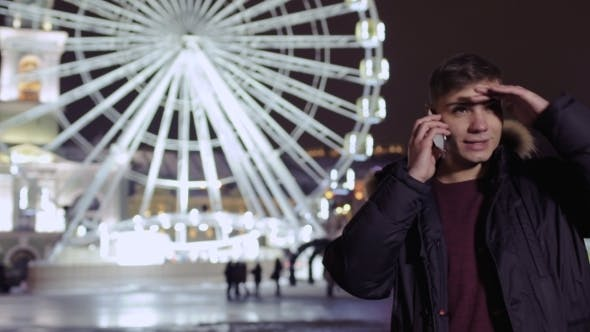 Thumbnail for Young Guy Talks on Phone and Waits Friend Near Ferris Wheel