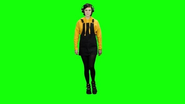 Thumbnail for Teenage Girl Walks Down the Street Wearing Headphones . Green Screen