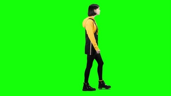 Thumbnail for Teen Is Walking Down the Street and Waving Hello . Green Screen. Side View