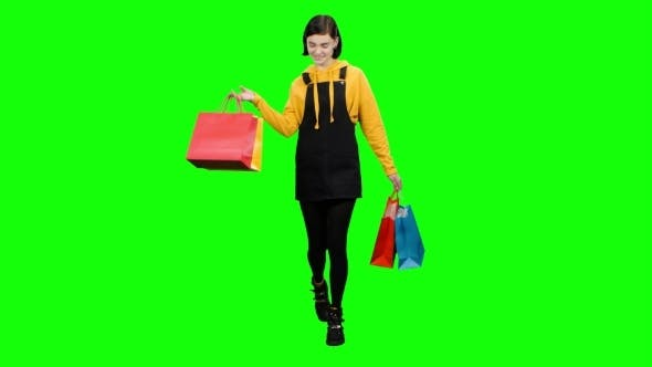 Thumbnail for Teen Is Walking Along the Street with Packages in Her Hands. Green Screen