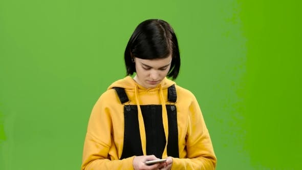 Thumbnail for Girl Is Typing a Message on Her Smartphone. Green Screen