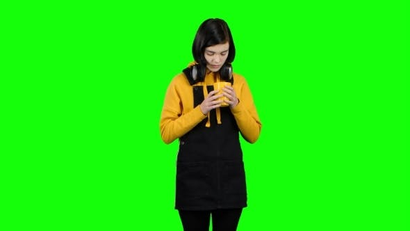 Thumbnail for Girl in a Jumpsuit Drinks Tea From a Yellow Glass. Green Screen
