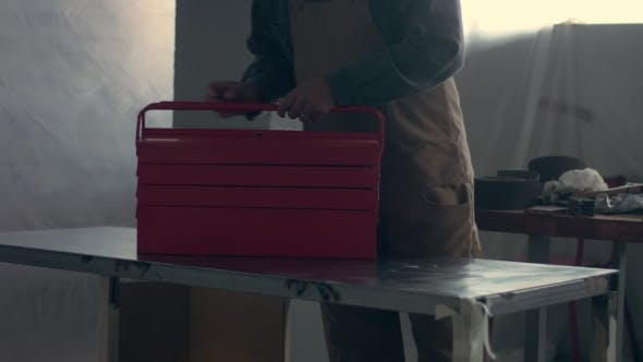 Thumbnail for Worker in His Garage with a Red Tool Storage Box