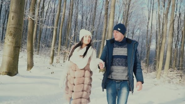 Cover Image for Couple Walking through the Winter Forest