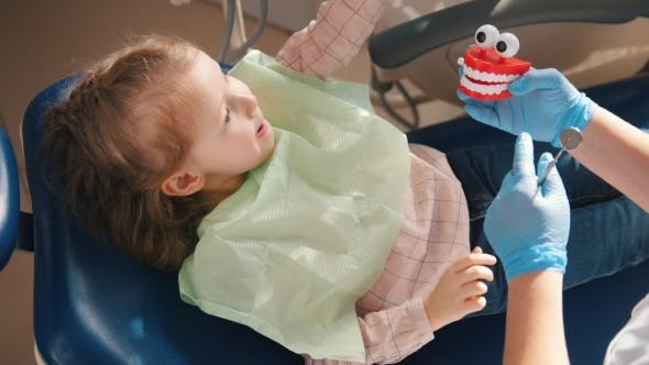 Thumbnail for Little Girl Sitting in Dental Chair Playing with Dental Tools and Toys