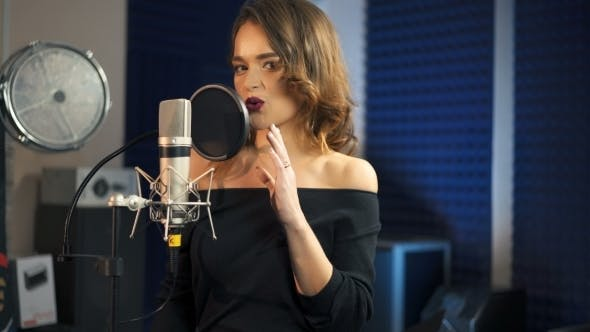 Thumbnail for Beautiful Woman Singing Into a Large Microphone. Professional Recording Studio.