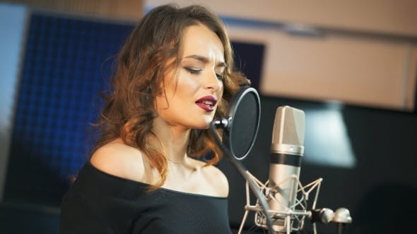 Thumbnail for Beautiful Woman Singing Into a Large Microphone. Professional Recording Studio