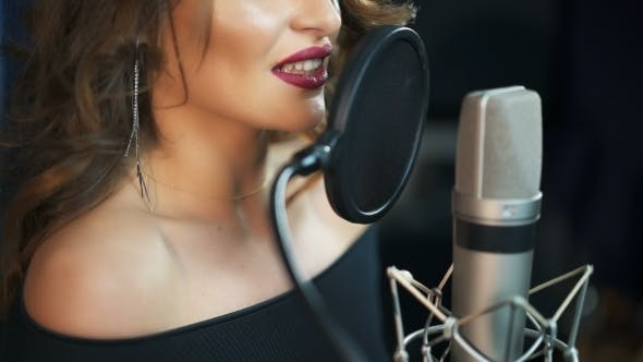 Thumbnail for Young Girl Singing Into a Microphone in a Studio