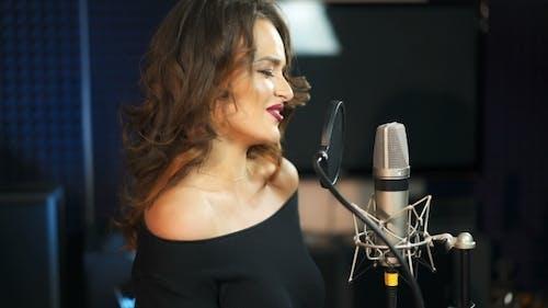 Young Female Singer Recording Album im professionellen Studio. Frau singt ein Lied in Musik