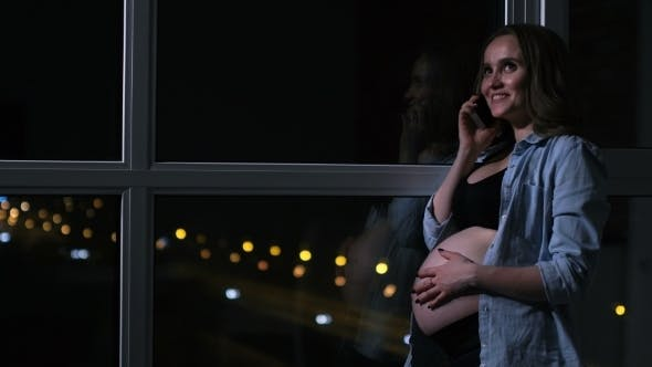 Cover Image for A Pregnant Woman in the Night Talking on the Mobile Phone Hands Touching the Stomach