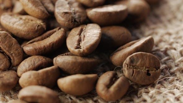 Thumbnail for Eine Handvoll braun, geröstete Kaffeebohnen auf Sackleinen Sacking Hintergrund, Rotation