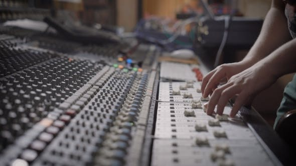 Thumbnail for Sound Engineer Is Moving Levers of a Multitrack Mixing Console in the Control Room During a
