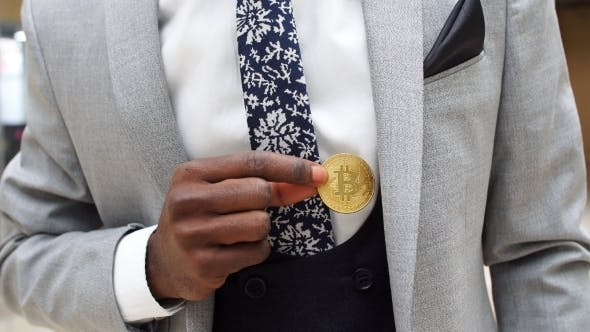 Thumbnail for Black Man Wearing Business Suit Holding Half Gold Bitcoin From Pocket.