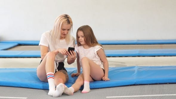 Thumbnail for Mother And Her Daughter Sitting on Trampoline in Fitness Park