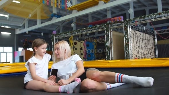 Thumbnail for Mother and Girl Using Phone in Gym for Watching Video How Do Jumping Exercise