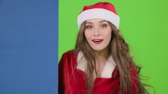Thumbnail for Santas Assistant Looks out of the Blue Board and Shows a Thumbs down