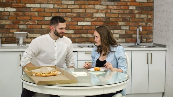 Thumbnail for Man and Pregnant Woman Eating Pizza at Home in Their Kitchen Poor Diet Fatty Foods Obesity