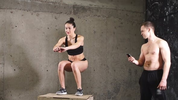 Thumbnail for Woman Jumping on Fit Box With Male Trainer at Gym