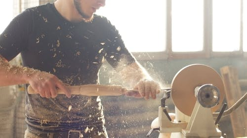 Attractive Carpenter Working on Woodworking Lathe Machine in The Carpenter Workshop
