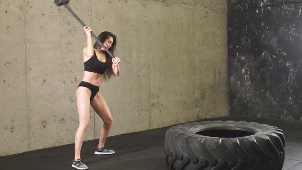Thumbnail for Girl Doing Sledgehammer Workout